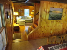 Lake House Log House Maine Lake Shore Boats Fishing Swim Spa, From dining area to living room, with stairs to upper level, on Sand Pond in Maine - Lakehouse Vacation Rental - Lake Home for rent on LakeHouseVacations.com